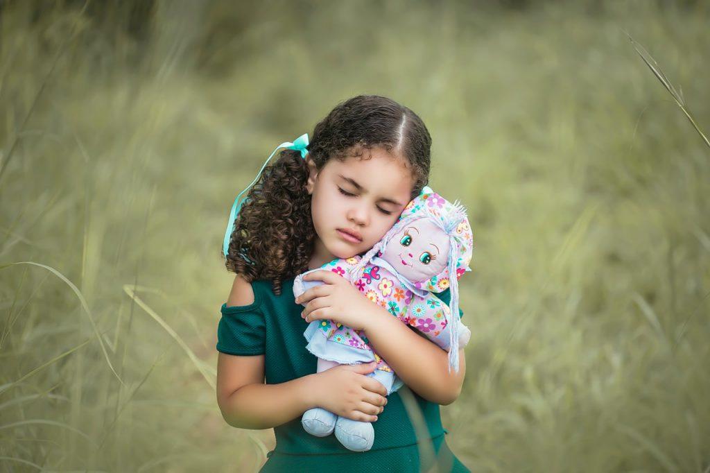 petite fille qui serre sa poupée dans ses bras