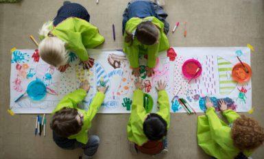 5 enfant qui dessinent sur une grande feuille blanche