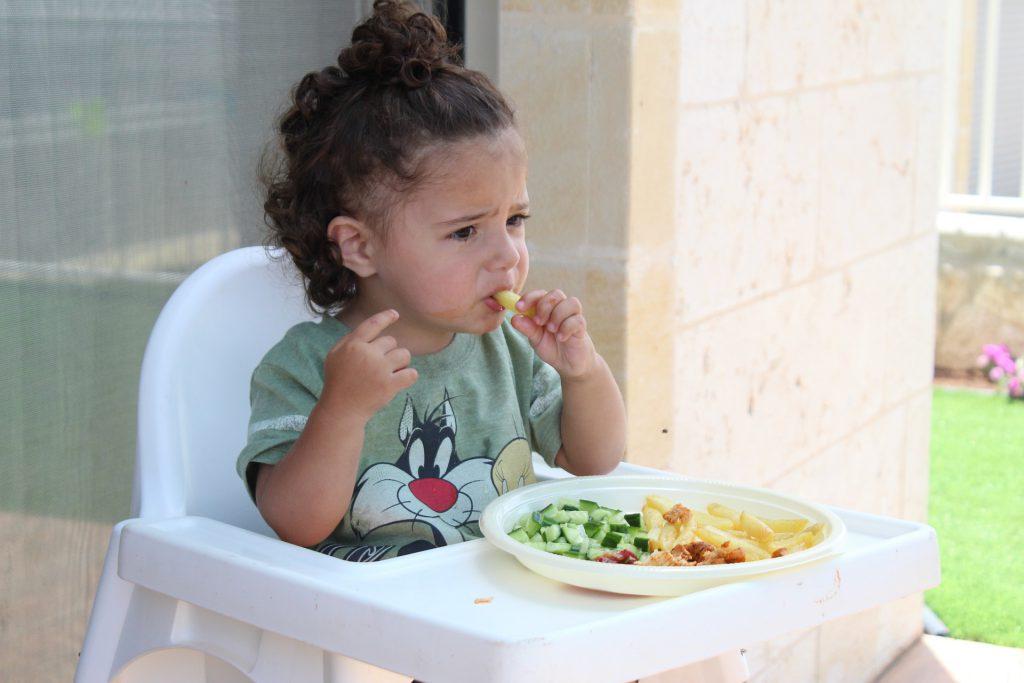 Bébé sur sa chaise haute en train de manger