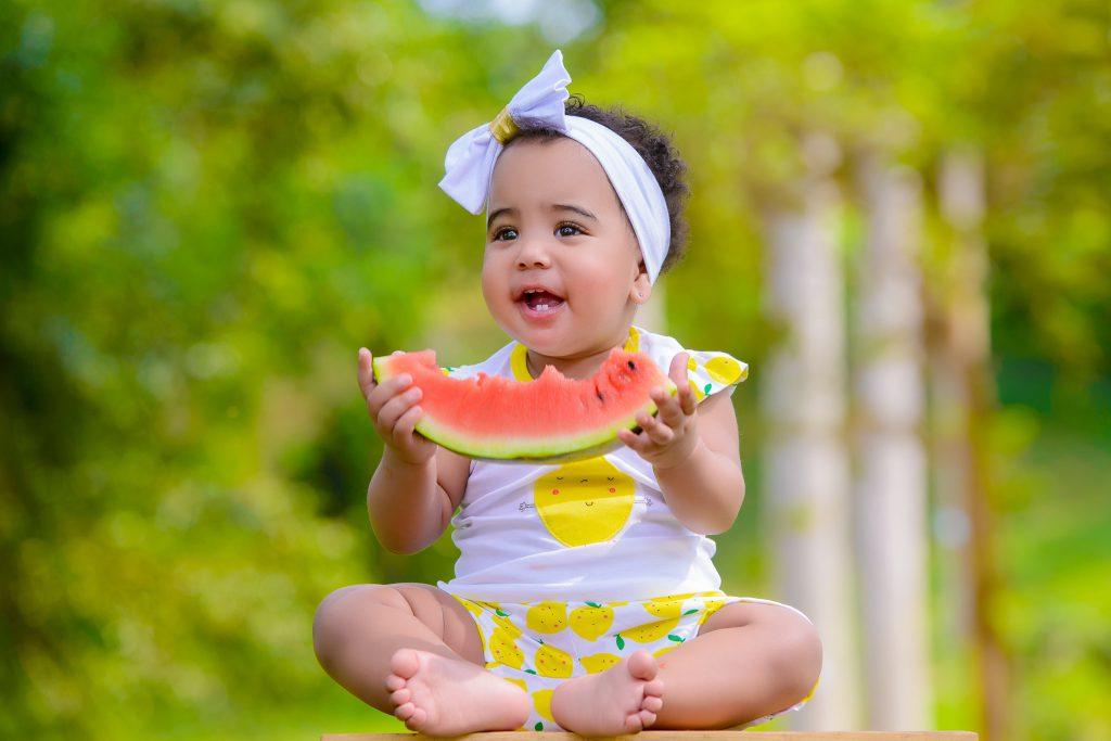 Petite fille tenant un morceau de pastèque