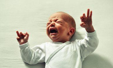 Un bébé sur un lit blanc qui pleure